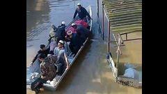 عکس / پیکر مادر 2 شهید آق قلا با قایق تشییع شد/ خانه او در محاصره سیل بود