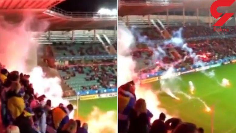 پرتاب خطرناک مواد آتشزا به زمین فوتبال + فیلم
